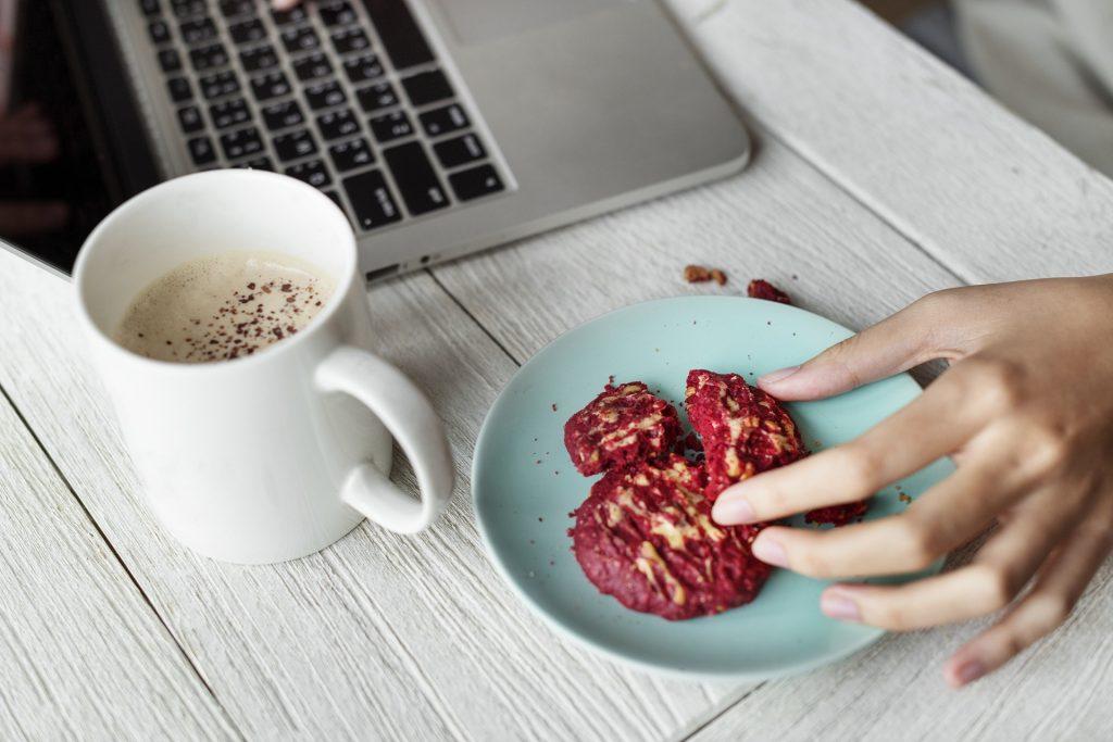 Une femme mangeant des cookies et buvant un café devant son ordinateur