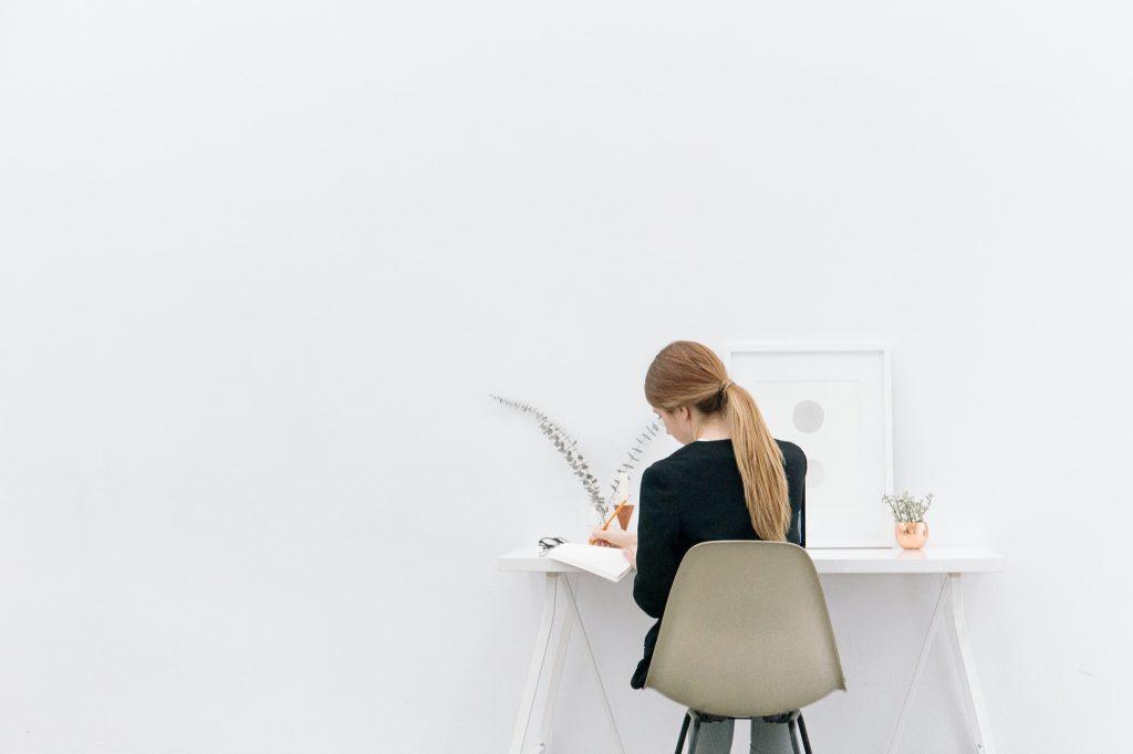 Une femme travaillant sur un petit bureau à la décoration minimaliste