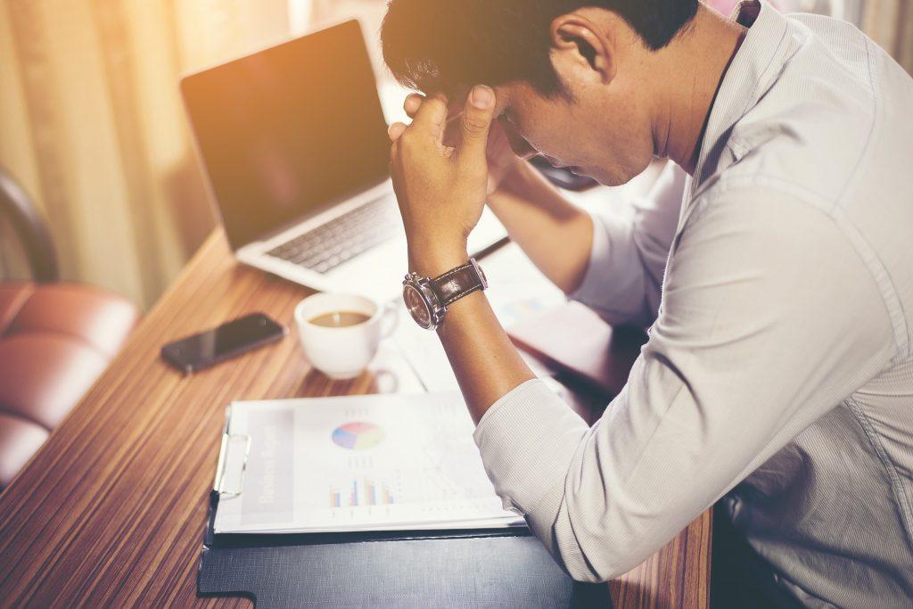 Un homme stressé par son travail assis devant un ordinateur