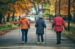 trois femmes qui marchent avec des bâtons de marche