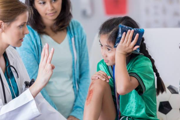 Petite fille souffrant d'un traumatisme crânien après une chute auscultée par un médecin