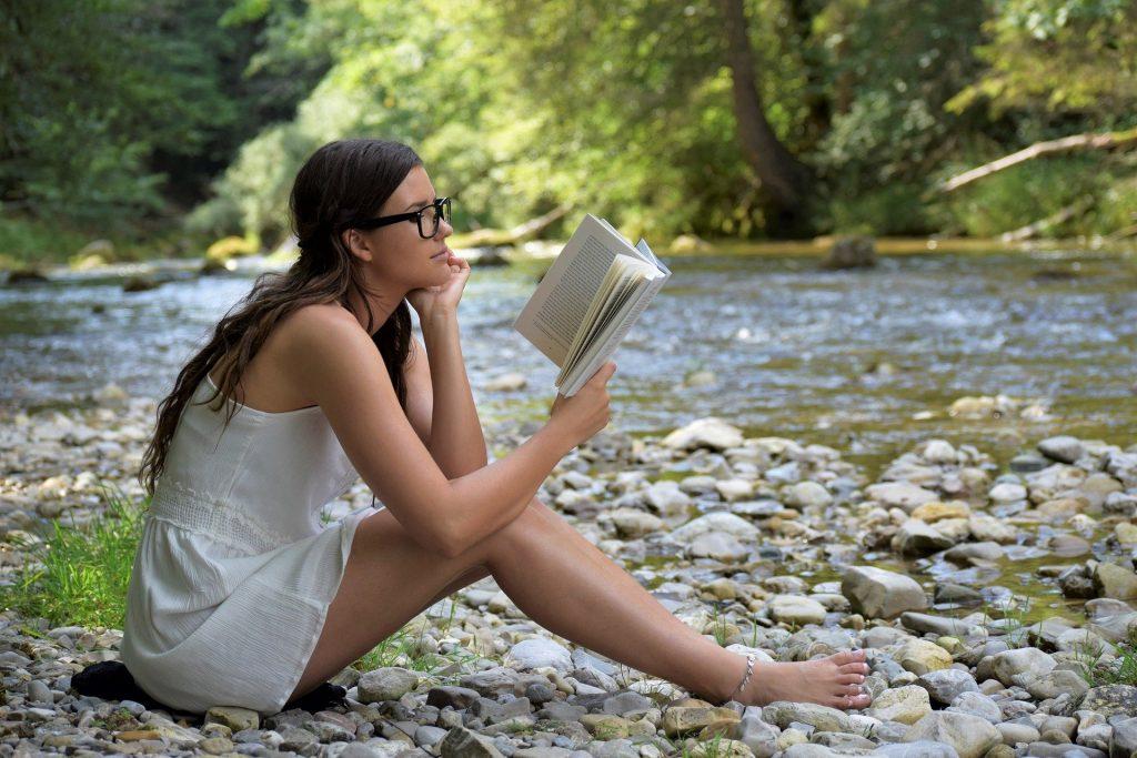 Jeune femme qui lit assise au bord d'une rivière