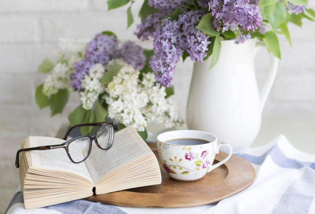 Livre posé sur une table à côté d'un bouquet de fleurs et d'une tasse
